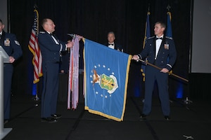 Photo of 119th Wing leaders placing an Air Force Outstanding Unit Award streamer on the unit guidon during a formal ceremony at the Hilton Garden Inn, Fargo, N.D., March 7, 2020.