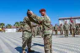 Lt. Col. David E. Moulton, commander of the 1st Squadron,112th Cavalry Regiment, Texas National Guard, and Command Sgt. Maj. Bradley A. Sutton, the 1-112th senior enlisted advisor, roll and uncase their colors to signify the start of their mission at a transfer of authority ceremony on South Camp, in Sharm el-Sheikh, Egypt, March 8, 2020. The 1-112th assumes responsibility as the 67th rotational United States Army unit in support of the Multinational Force and Observers peacekeeping mission.