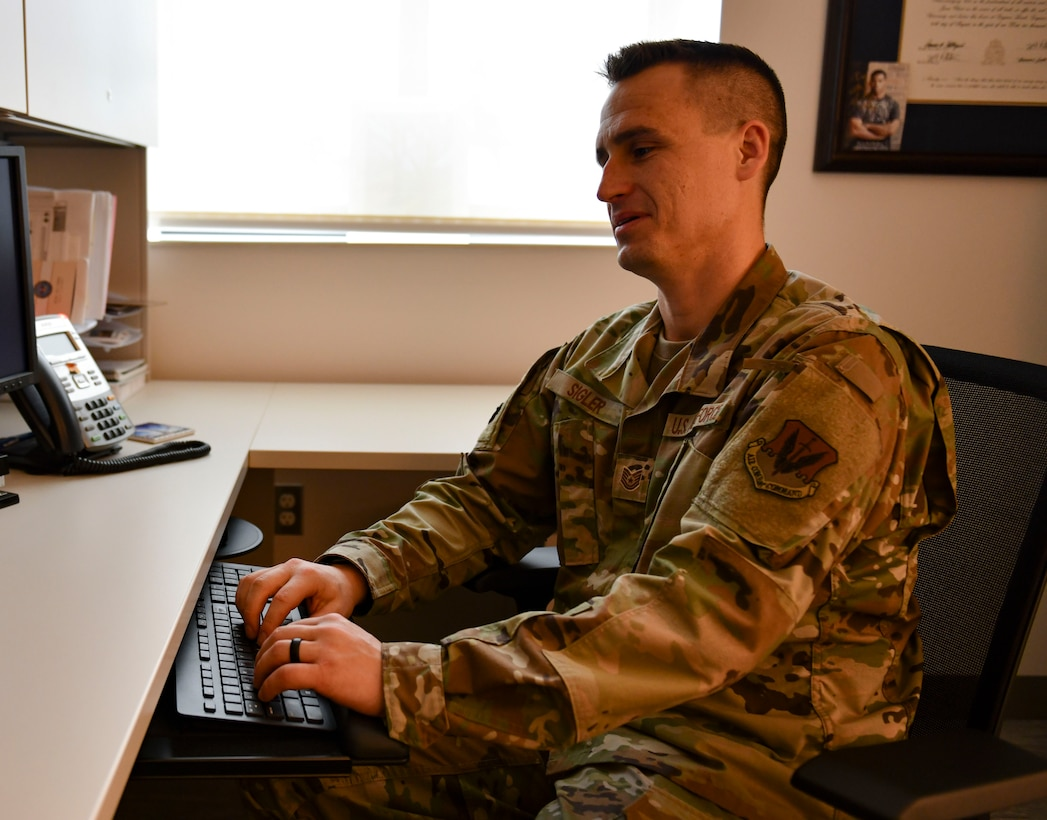 U.S. Air Force Tech. Sgt. James Sigler, 325th Operational Medical Readiness Squadron mental health flight chief, types on a computer at Tyndall Air Force Base, Florida, March 4, 2020. Sigler is in charge of the mental health clinic's daily operations and makes sure the patients get the care they need. (U.S. Air Force photo by Senior Airman Stefan Alvarez)
