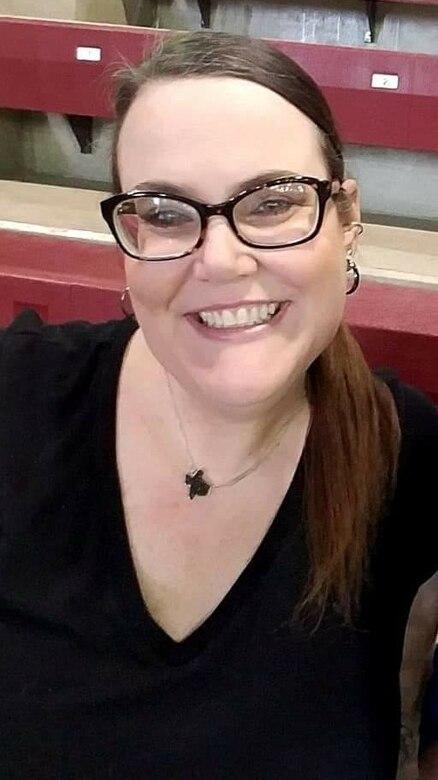 Woman sitting on bleachers wearing a black top