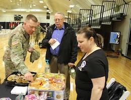 Lori Rozhon, 1st Theater Sustainment Command (TSC) Soldier Family Readiness Group (SFRG) leader, chats with Capt. Kevin Coulter, Special Troops Battalion (STB) chaplain, 1st TSC, and Jim Peters, military and family life counselor, 1st TSC, while manning the snack table at a redeployment ceremony for the 18th Financial Management Support Center on Feb. 26, 2020 at Sadowski Center, Fort Knox, Ky. (U.S. Army photo by Spc. Zoran Raduka).