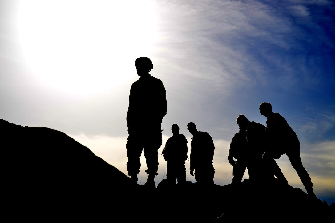 A group of soldiers stand in silhouette on a hill.