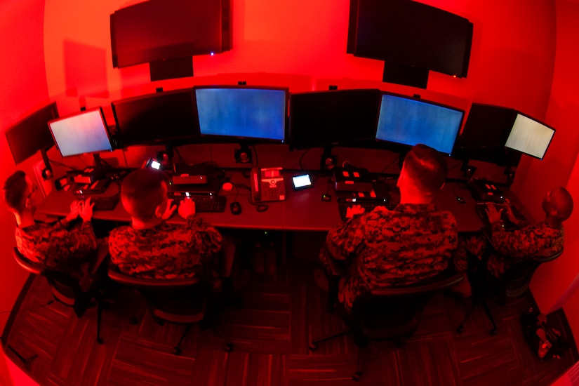 A fisheye view of three service members looking at computer monitors in what appears to be a small room.