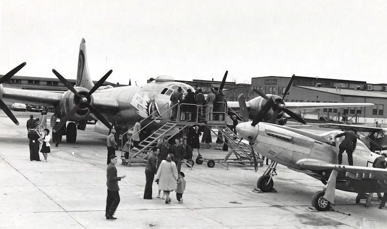 A dozen or more patrons admire static displays of aircraft on the  airfield.