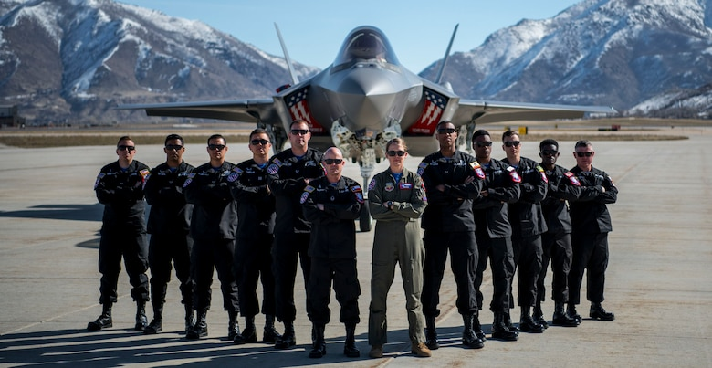 A F-35A Lightning II Demonstration Team group picture in front of an F-35A.