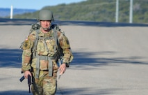 White male in green camouflage uniform and gray helmet on a road.