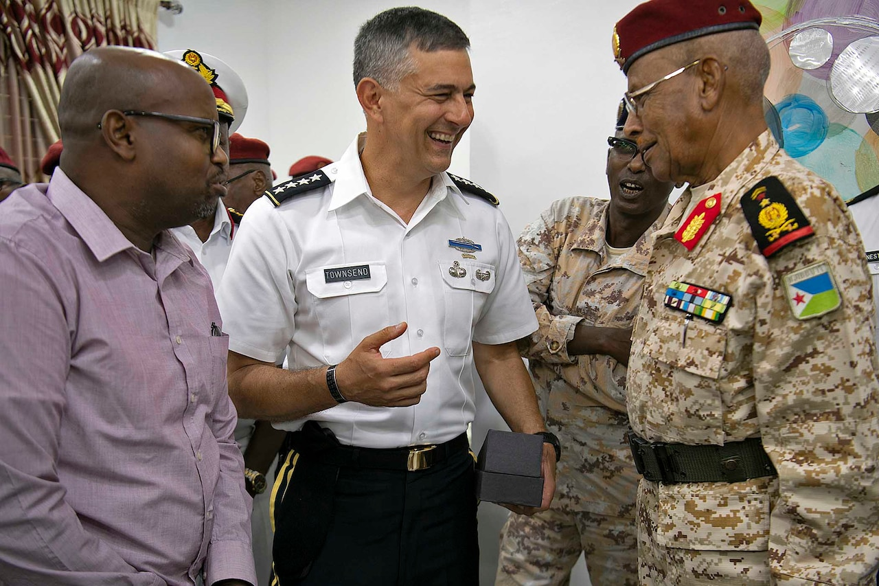 Two military men speak to one another.