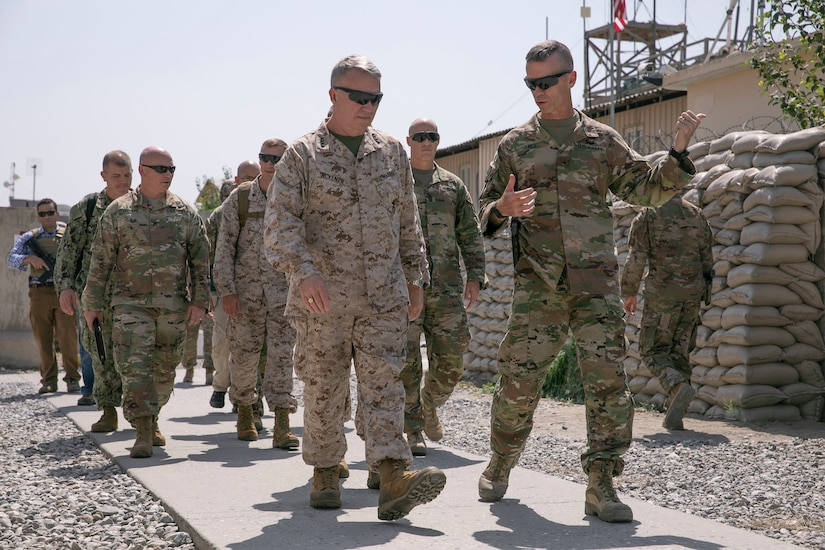 A group of military service members dressed in fatigues walk on a  sidewalk.