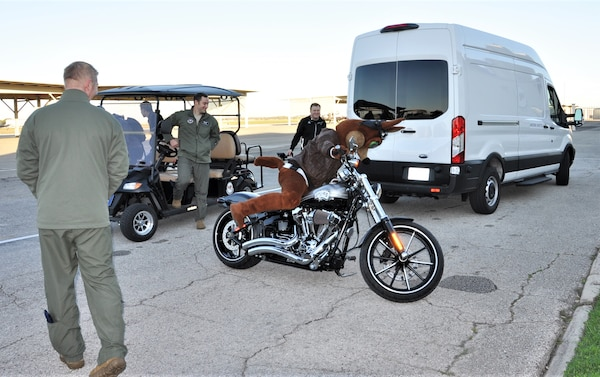 The Spurs Coyote climbs on his custom Harley on the Joint Base San Antonio-Randolph, Texas flight line February 25 where Regular Air Force, Air Force Reserve, and civilian Airmen from the 340th Flying Training Group headquarters, 39th Flying Training Squadron T-6 Texan Flight, 12th Flying Training Wing Safety, 559th Flying Training Squadron T-6 team, and 3rd Combat Camera Squadron (JBSA-Lackland) members, and the NBA San Antonio Spurs production crew worked to put the Coyote through the pilot training process. Video footage will be used for a Spurs Military Appreciation video to be shown during the March 10 game. (U.S. Air Force photo by Janis El Shabazz)