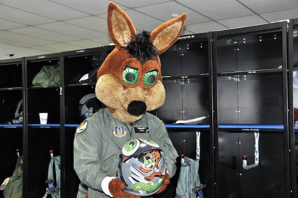 The Spurs Coyote checks out his customized helmet in the 559th Training Squadron locker room at Joint Base San Antonio-Randolph, Texas February 25 where Regular Air Force, Air Force Reserve, and civilian Airmen from the 340th Flying Training Group headquarters, 39th Flying Training Squadron T-6 Texan Flight, 12th Flying Training Wing Safety, 559th Flying Training Squadron T T-6 team, and 3rd Combat Camera Squadron (JBSA-Lackland) members, and the NBA San Antonio Spurs production crew worked to put the Coyote through the pilot training process. Video footage will be used for a Spurs Military Appreciation video to be shown during the March 10 game.  (U.S. Air Force photo by Janis El Shabazz)