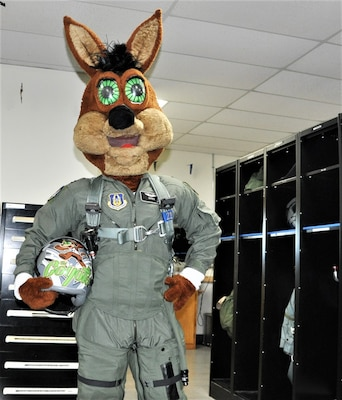 The Spurs Coyote poses with his customized helmet in the 559th Training Squadron locker room at Joint Base San Antonio-Randolph, Texas February 25 where Regular Air Force, Air Force Reserve, and civilian Airmen from the 340th Flying Training Group headquarters, 39th Flying Training Squadron T-6 Texan Flight, 12th Flying Training Wing Safety, 559th Flying Training Squadron T-6 team, and 3rd Combat Camera Squadron (JBSA-Lackland) members, and the NBA San Antonio Spurs production crew worked to put the Coyote through the pilot training process. Video footage will be used for a Spurs Military Appreciation video to be shown during the March 10 game.  (U.S. Air Force photo by Janis El Shabazz)