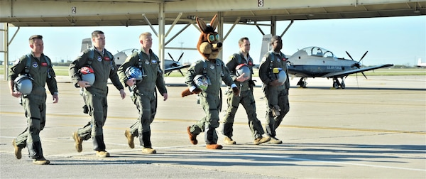 The Spurs Coyote and his mission teammates for the day walk to their planes at Joint Base San Antonio-Randolph, Texas February 25 where Regular Air Force, Air Force Reserve, and civilian Airmen from the 340th Flying Training Group headquarters, 39th Flying Training Squadron T-6 Texan Flight, 12th Flying Training Wing Safety, 559th Flying Training Squadron T-6 team, and 3rd Combat Camera Squadron (JBSA-Lackland) members, and the NBA San Antonio Spurs production crew worked to put the Coyote through the pilot training process. Video footage will be used for a Spurs Military Appreciation video to be shown during the March 10 game. (U.S. Air Force photo by Debbie Gildea)