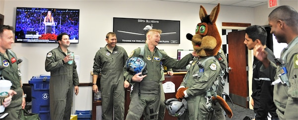 340th Flying Training Group instructor pilot – Lt. Col. Mark Pasierb (center) chats with the Spurs Coyote in the 559th Training Squadron step room February 25 following the Coyote's simulated flight at Joint Base San Antonio-Randolph, Texas where Regular Air Force, Air Force Reserve, and civilian Airmen from the 340th Flying Training Group headquarters, 39th Flying Training Squadron T-6 Texan Flight, 12th Flying Training Wing Safety, 559th Flying Training Squadron T-6 team, and 3rd Combat Camera Squadron (JBSA-Lackland) members, and the NBA San Antonio Spurs production crew worked to put the Coyote through the pilot training process. Video footage will be used for a Spurs Military Appreciation video to be shown during the March 10 game. (U.S. Air Force photo by Janis El Shabazz)