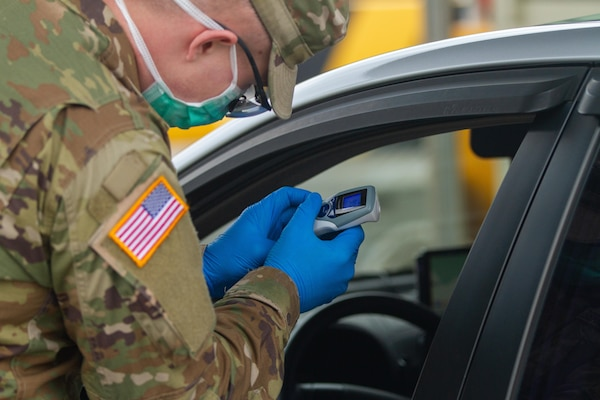 A soldier checks a thermometer reading.