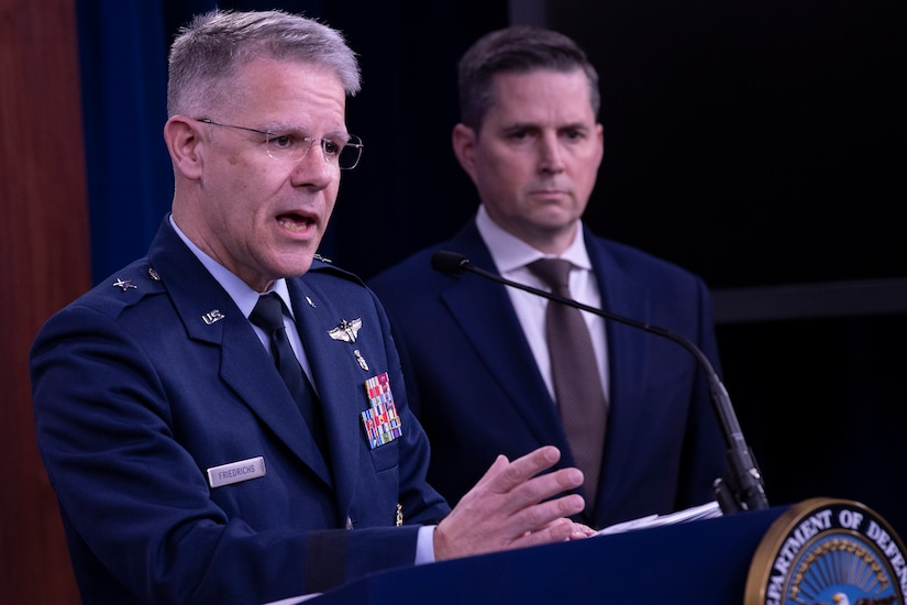 An Air Force officer speaks from behind a podium. A civilian man stands to his left.