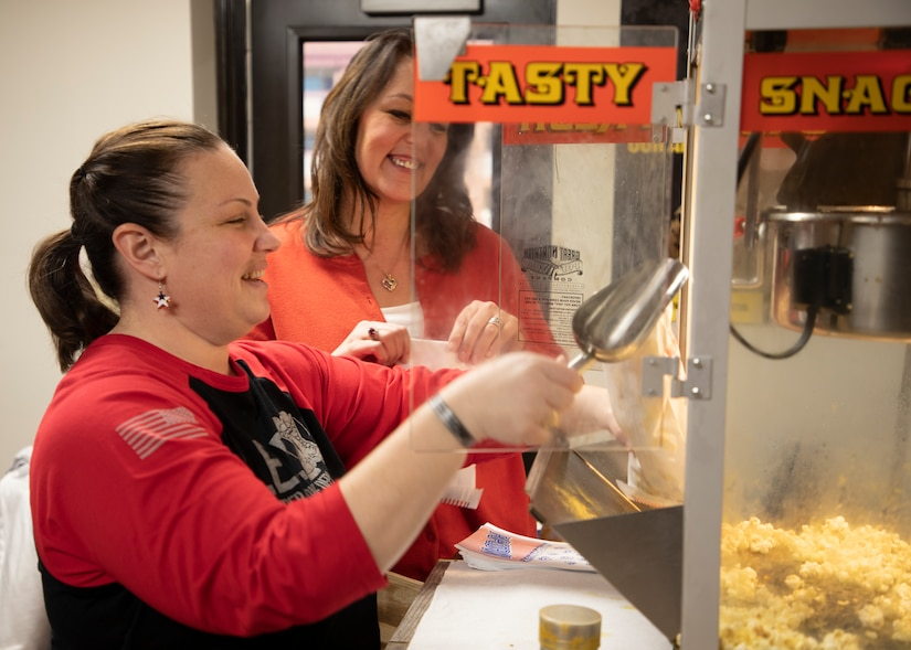 Lori Rozhon, Soldier Family Readiness Group (SFRG) leader for the 1st Theater Sustainment Command (TSC), scoops popcorn into a bag for a weekly fundraiser Feb. 27, 2020 at Fowler Hall, Fort Knox, Ky., as Theresa Scott, family readiness support assistant, 1st TSC looks on. The SFRG sells popcorn and other snacks to raise money for events for Soldiers, civilians and families of the 1TSC. (U.S. Army photo by Wendy Arevalo).