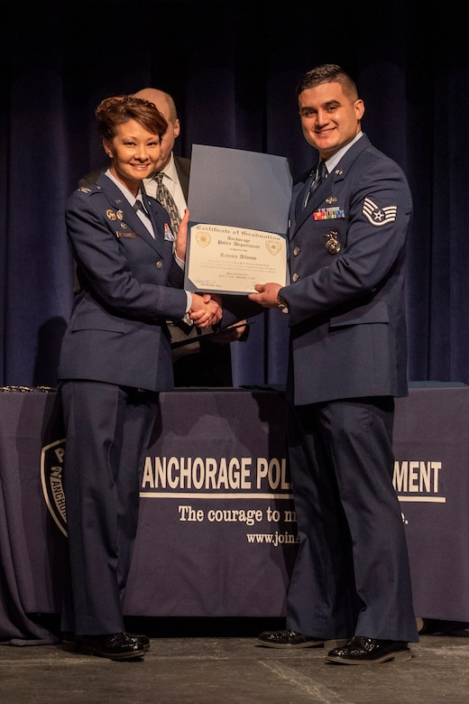 U.S. Air Force Staff Sgt. Ramses Alfonso, 673d Security Forces Squadron lead patrolman, receives a certificate of completion for graduating Anchorage Police Department 19-1 Academy from U.S. Air Force Col. Patricia Csànk, Joint Base Elmendorf-Richardson and 673d Air Base Wing commander, in Anchorage, Alaska, Dec. 5, 2019. Alfonso earned the Distinguished Honor Graduate Award, Class Valedictorian, Top Shooter, and Top Defensive Driver in the Emergency Vehicle Operations Course. The partnership between the squadron and the Anchorage Police Department provides Airmen with a clearer understanding of municipal police procedures as well as builds contacts with all partner law enforcement agencies who participate in the academy.