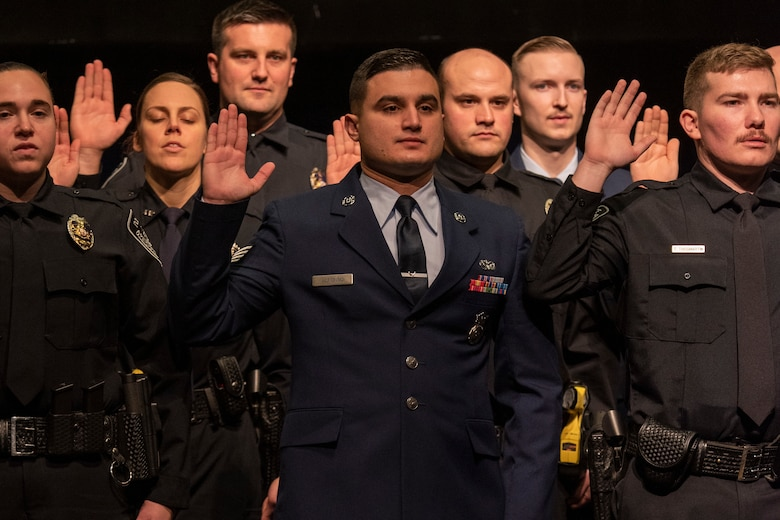 U.S. Air Force Staff Sgt. Ramses Alfonso (center), 673d Security Forces Squadron lead patrolman, swears in at the Anchorage Police Department 19-1 Academy graduation in Anchorage, Alaska, Dec. 5, 2019. Alfonso earned the Distinguished Honor Graduate Award, Class Valedictorian, Top Shooter, and Top Defensive Driver in the Emergency Vehicle Operations Course. The partnership between the squadron and the Anchorage Police Department provides Airmen with a clearer understanding of municipal police procedures as well as builds contacts with all partner law enforcement agencies who participate in the academy.