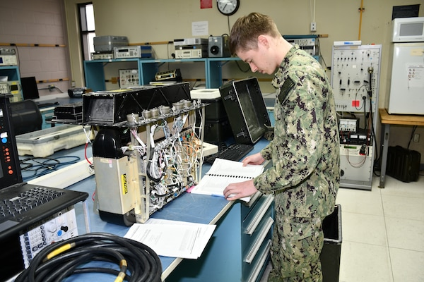 "Electronics Technician Second Class Samuel Walling, Calibration Technician for the Mid-Atlantic Regional Calibration Center, troubleshoots and repairs a Navigation Communication Test Set for Fleet Logistics Support Squadron 40 (VFA-40) ""Rawhides"" in direct support of flight line readiness."