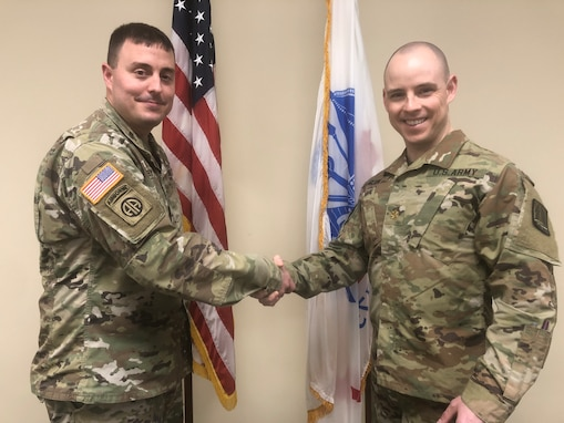 U.S. Army Reserve Maj. Brenden Glynn, recently promoted, and a cyber qualified officer currently assigned to the Northeast Cyber Protection Center, U.S. Army Reserve Cyber Protection Brigade, 335th Signal Command (Theater), is congratulated by Lt. Col. Christopher Rowey, former operations officer for Northeast, January 28