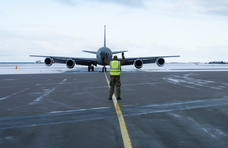 Airmen taxiing military refueling aircraft.