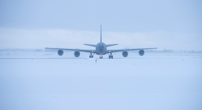 Military refueling taxis on snowy runway.