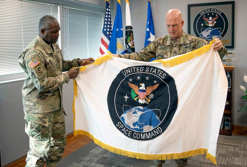 Black officer presents a large unit flag depicting the Space Command with an eagle on top of the planet Earth to a white officer.