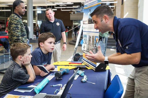 Cartridge Actuated Device/Propellant Actuated Device (CAD/PAD) Fleet Support Team/Mishap Investigation Support Team lead Nick Schombs discusses CAD/PAD technology with Mason Whetzel, 5,(bottom left) and Dylan Whetzel, 8, during the annual HITS Expo at St. Charles High School, Saturday. (Photo by Matt Poynor)