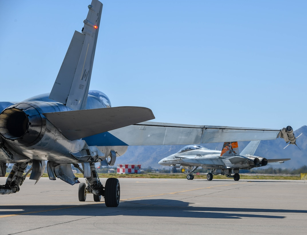 Two Royal Canadian air force CF-18 Hornets, assigned to the 433rd Tactical Fighter Squadron in Canadian Forces Base Bagotville, Quebec, Canada, taxi into position for takeoff Feb. 25, 2020, at Luke Air Force Base, Ariz.
