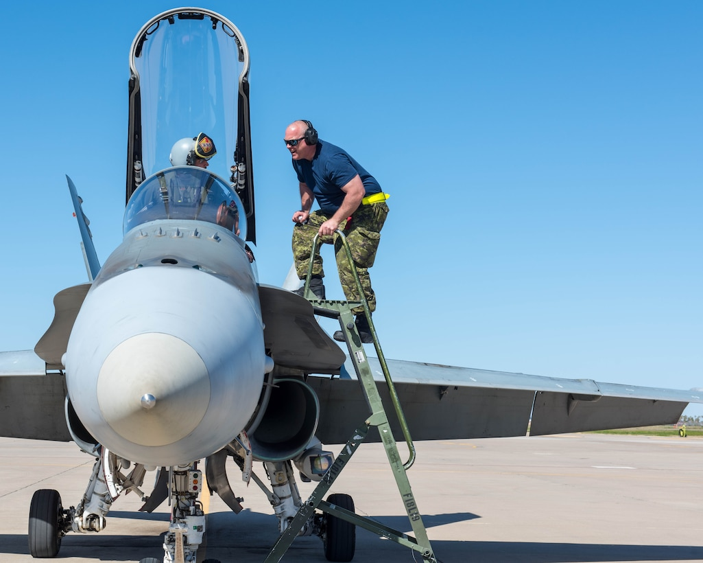 A Royal Canadian air force CF-18 Hornet pilot and crew chief, assigned to the 433rd Tactical Fighter Squadron in Canadian Forces Base Bagotville, Quebec, Canada, prepare for takeoff Feb. 25, 2020, at Luke Air Force Base, Ariz.