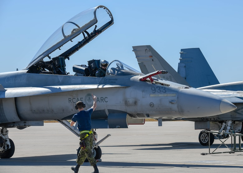 A Royal Canadian air force crew chief, assigned to the 433rd Tactical Fighter Squadron in Canadian Forces Base Bagotville, Quebec, Canada, gives a CF-18 Hornet pilot a thumbs up Feb. 25, 2020, at Luke Air Force Base, Ariz.