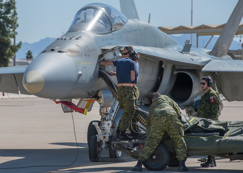 Royal Canadian air force maintainers, assigned to the 433rd Tactical Fighter Squadron in Canadian Forces Base Bagotville, Quebec, Canada, load ammunition onto a CF-18 Hornet, Feb. 25, 2020, at Luke Air Force Base, Ariz.