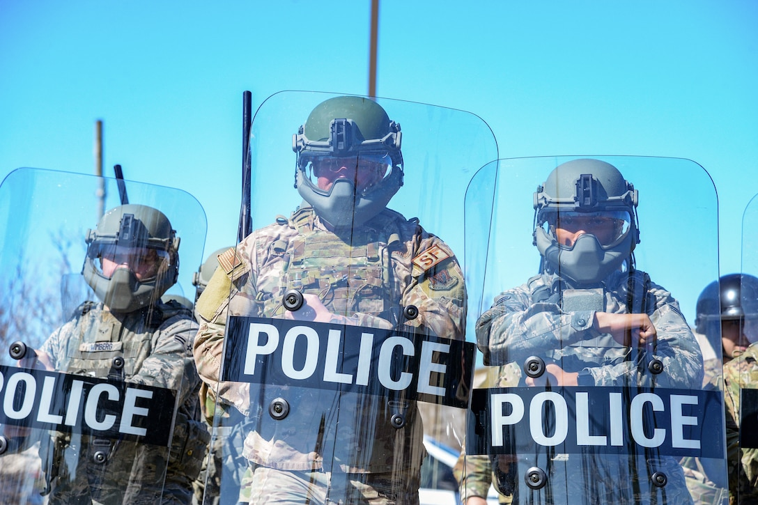 A picture of Airmen marching in formation with riot gear.