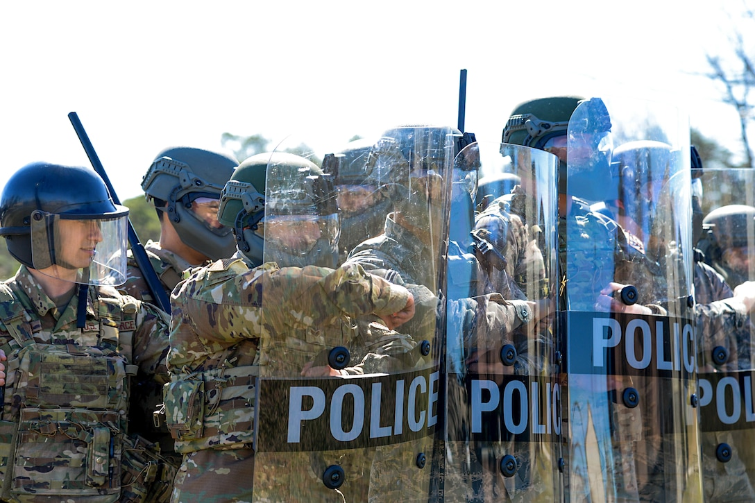 A picture of Airmen forming a barrier with riot shields.