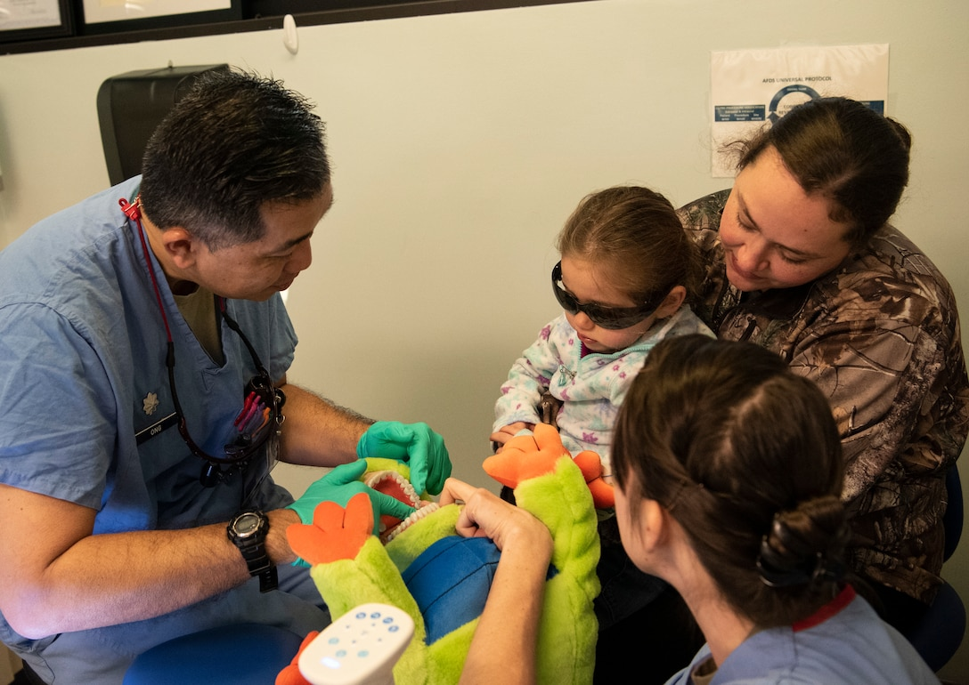 Dental clinic Airmen demonstrate to a child how they will count her teeth.