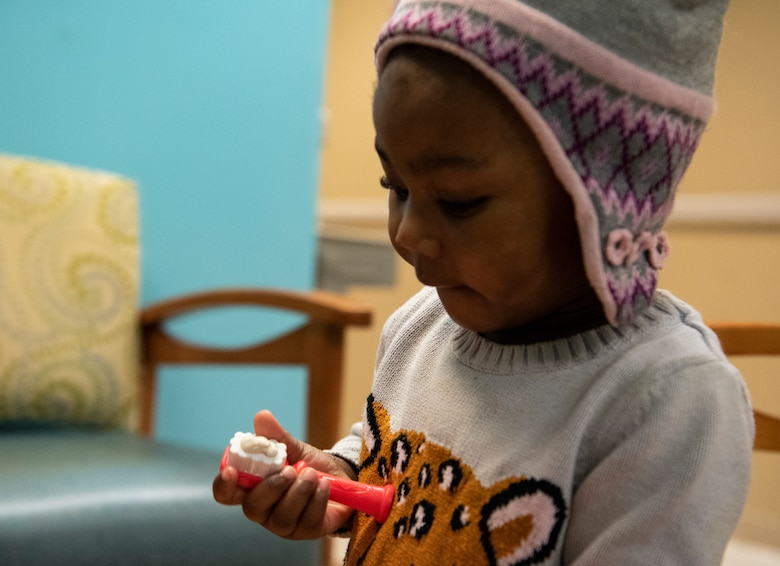 Child plays with toy toothbrush.