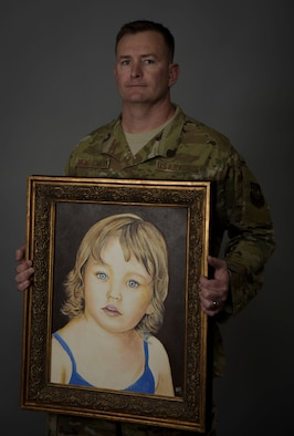 A man holds a painting of his daughter.