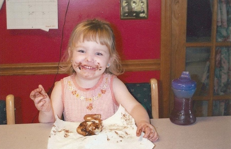 A small girl eats chocolate cake and smiles.