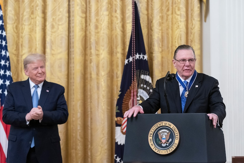 One man speaks from behind a podium while another listens.