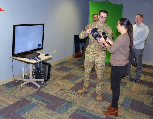 Staff Sgt. Tyler Williams, Career Enlisted Aviator Center of Excellence basic boom operator instructor, assists Laura Cabanilla, San Antonio Chamber/San Antonio Hispanic Chamber of Commerce co-chair Leadership San Antonio 44, don a virtual reality headset during an honorary commander tour of the 433rd Operations Group March 7, 2020 at Joint Base San Antonio-Lackland, Texas.