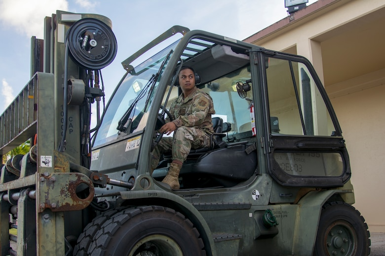 Picture of U.S. Air Force Staff Sgt. Jomar Cruz, 44th Aerial Port Squadron transportation specialist, observing his spotter as he operates a forklift during the first Patriot Express mission at Andersen Air Force Base, March 7, 2020.