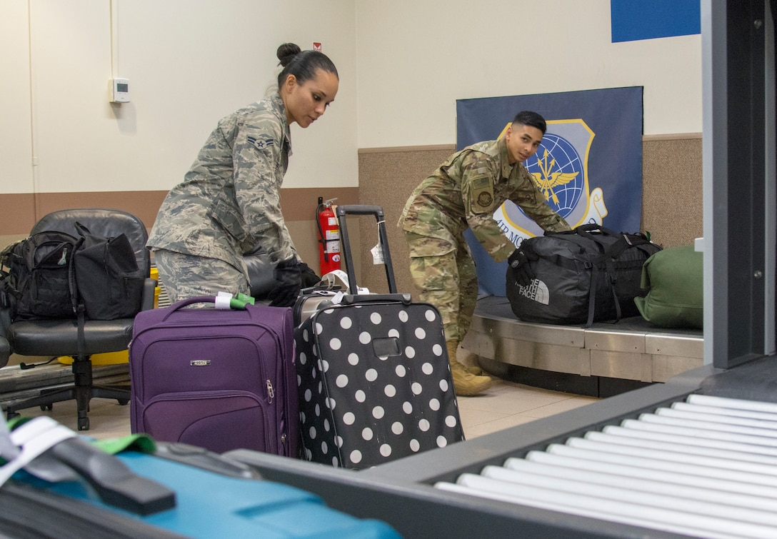 Picture of U.S. Air Force Airman 1st Class Camarin Perez, left, and Senior Airman Joshua San Agustin, 44th Aerial Port Squadron transportation specialists, moving baggage to a conveyor belt for loading onto an aircraft in support of the first Patriot Express mission at Andersen Air Force Base, Guam, March 7, 2020.