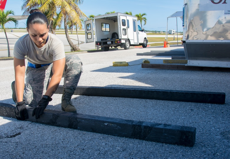 Picture of U.S. Air Force Airman 1st Class Camarin Perez, 44th Aerial Port Squadron transportation specialist, placing floor dunnage on the ground for cargo bins in support of the first Patriot Express mission to arrive at Andersen Air Force Base, Guam, March 7, 2020.