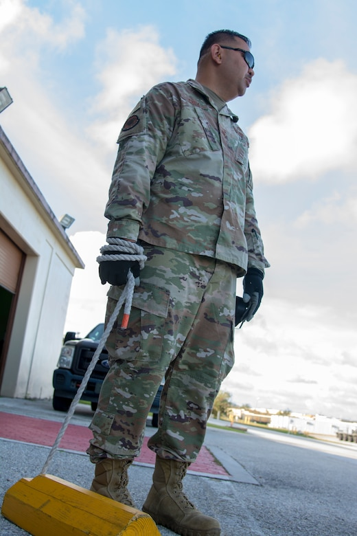 Picture of U.S. Air Force Master Sgt. Patrick Cruz, 44th Aerial Port Squadron transportation supervisor, waiting with a chock in hand while acting as a spotter and directing various transportation equipment during the first Patriot Express mission at Andersen Air Force Base, Guam, March 7, 2020.