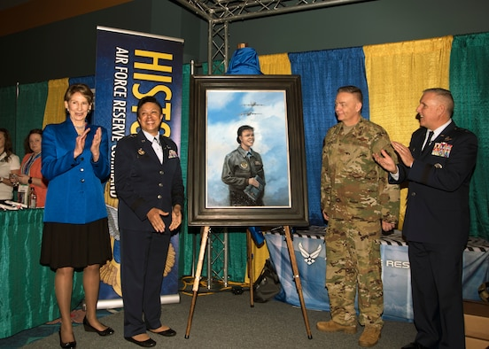 Image of Secretary of the Air Force Barbara Barrett, Lt. Gen. Stayce Harris (retired), Senior Master Sgt. Darby Perrin, heritage and combat artist and  Maj. Gen. John Flournoy, AFRC deputy commander unveiled a painting a portrait of Harris during the 2020 Women in Aviation Conference, March 6 in Orlando, Florida. The portrait shows Harris standing in a flight jacket with flight crew checklists in hand with a KC-135R and C-141-B flying overhead, both aircraft were flown by Harris. (U.S. Air Force photo by Staff. Sgt. Cierra Presentado)