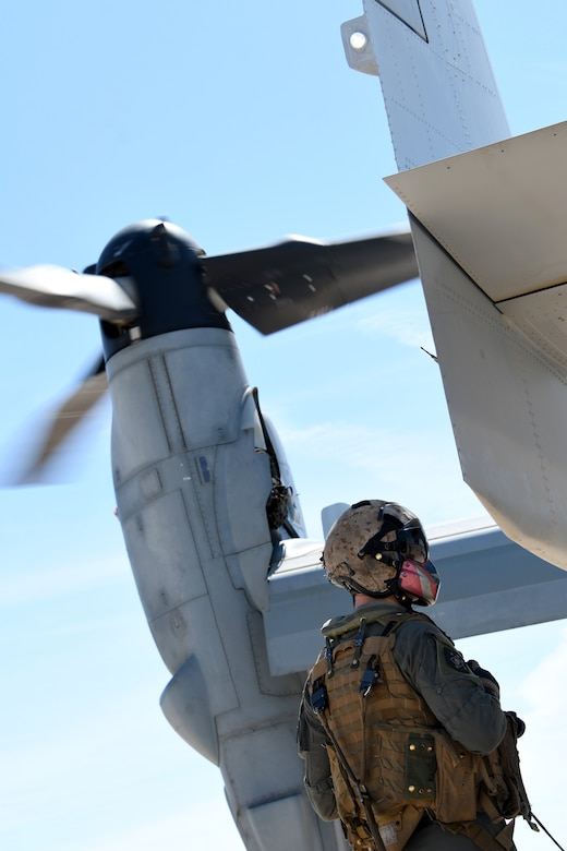 A photo of a Marine standing next to a MV-22B Osprey