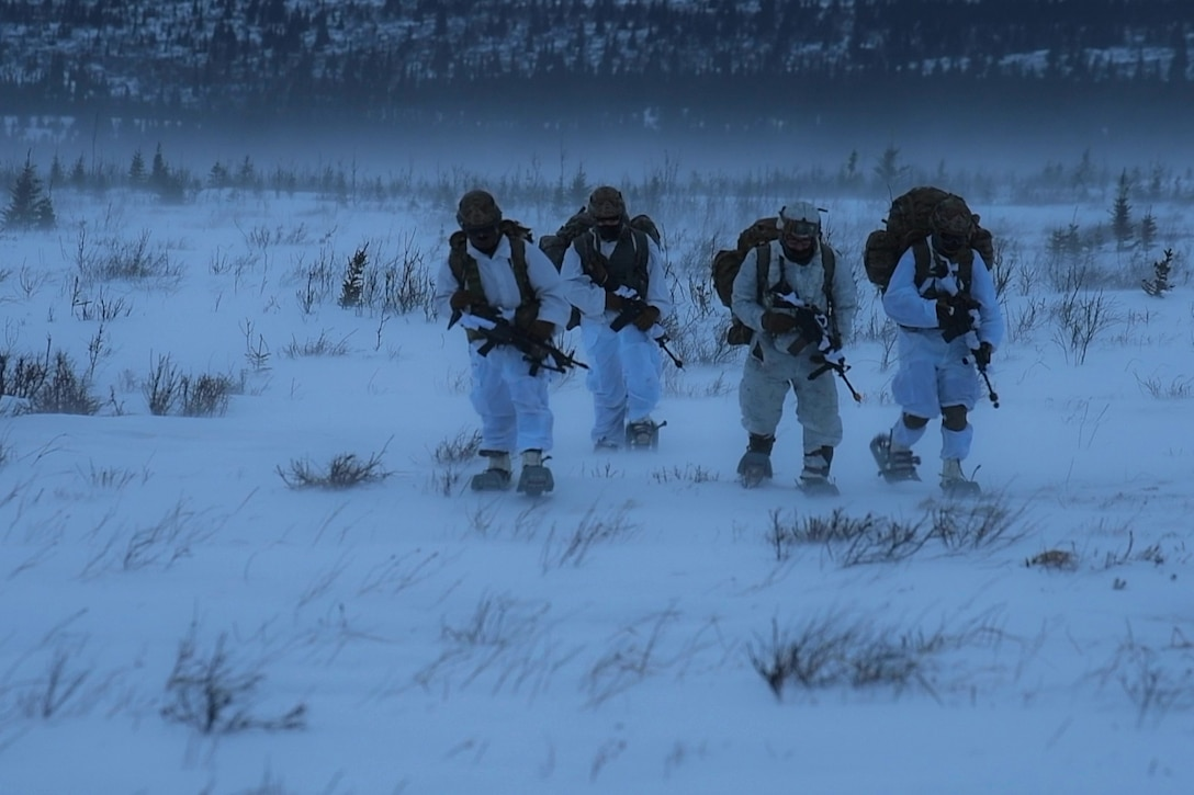 Paratroopers cross a snowy field.