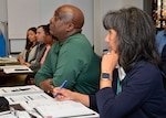 Kathy Atkins-Nuñez, far right, DLA Disposition Services South-East Region director, takes notes next to Joe Arnold, outgoing DLA Disposition Services Mid-America director, at the Mid-America Leadership Summit she attended to prepare for her new role as the next region director.