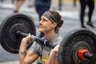 White female in gray and yellow t-shirt and black and white headbands holds barbell with eights