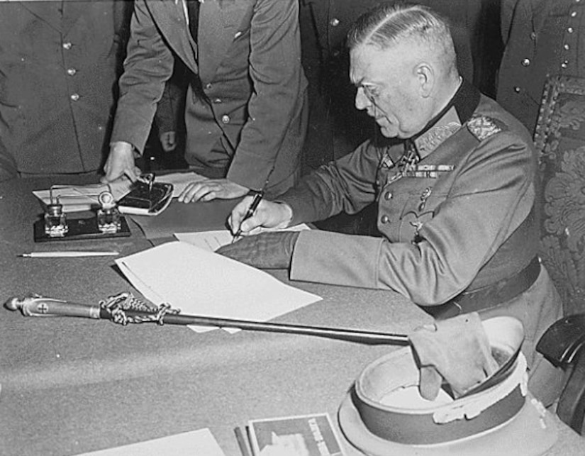 A military man signs some papers while others look on.